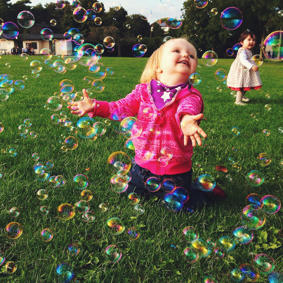Children playing with bubbles in the park