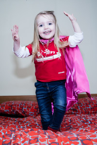 Girl wearing superhero cape jumping on bed
