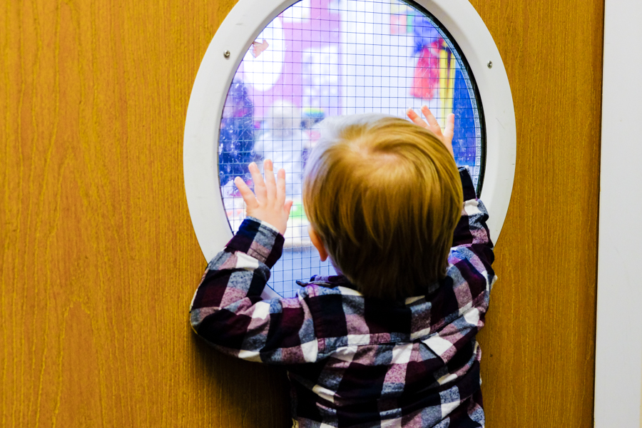 Little boy looking through the door at Co-op Nursery Maidenhead