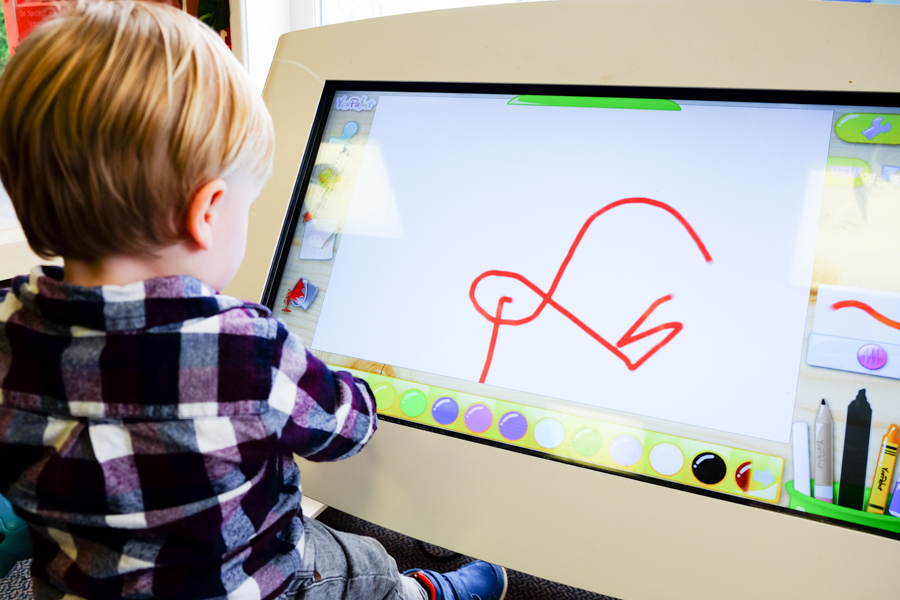 Child playing with large touch screen