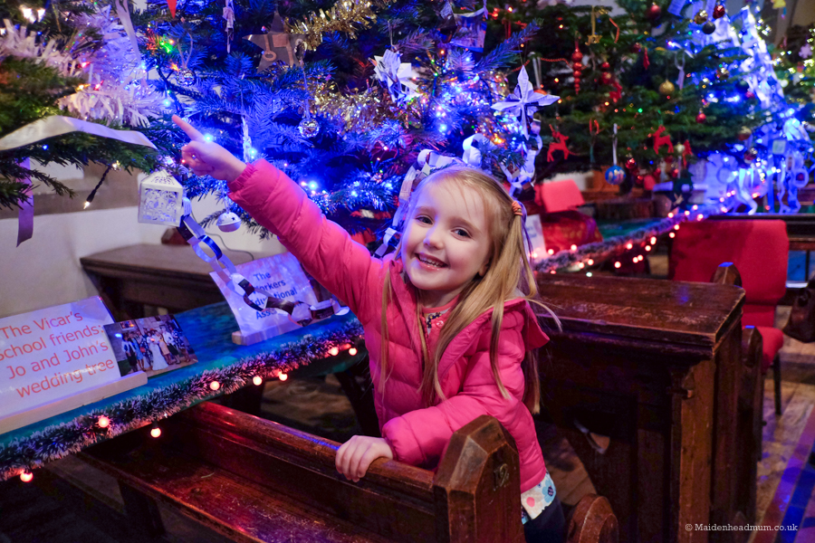 little girl looking at Christmas decorations at Christmas Tree festival maidenhead