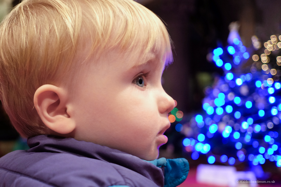 Little boy with Christmas Tree lights bokeh in the background.