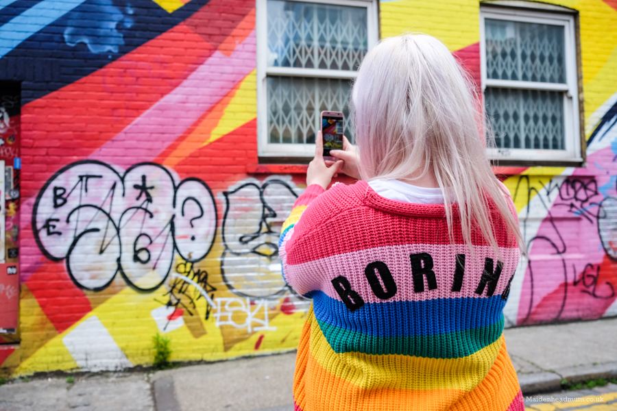 Photographer taking photo of street art wall in Shoreditch.