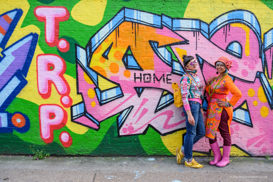 Bloggers posing in front of street art wall