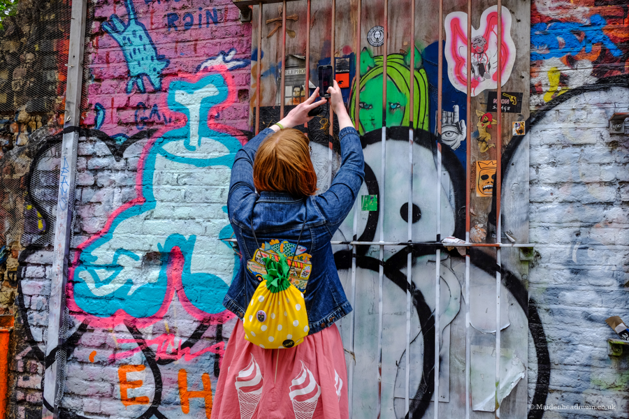 A blogger taking a photo of street art in shoreditch